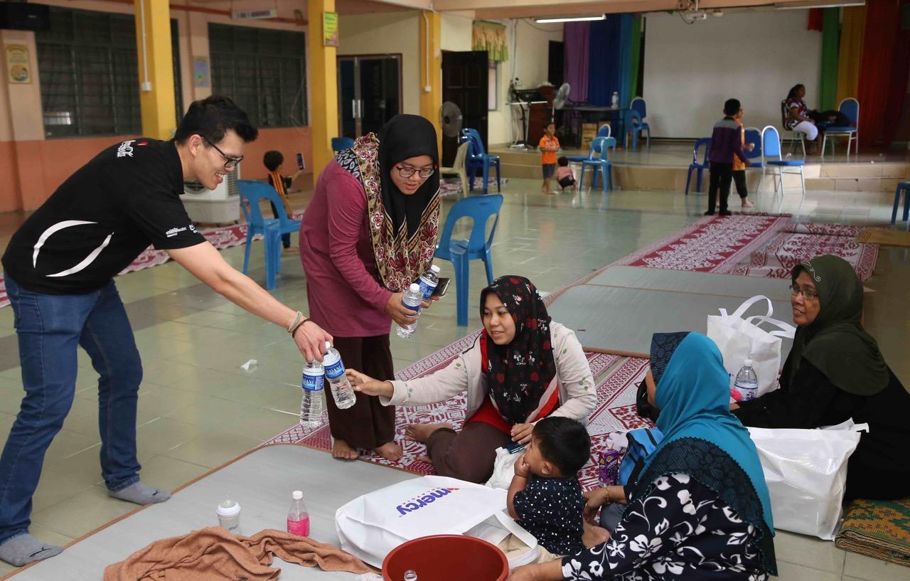 Para pekerja Coca-Cola mengagihkan air minuman Dasani kepada keluarga yang berlindung di SK Bertam Indah, Seberang Perai