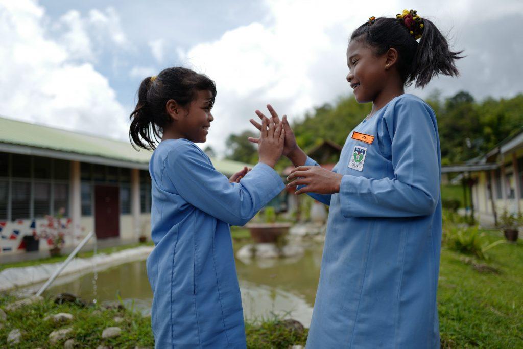 Dua orang pelajar Orang Asli di SK Pos Tenau gembira bermain 'Tepuk Amai-amai'.