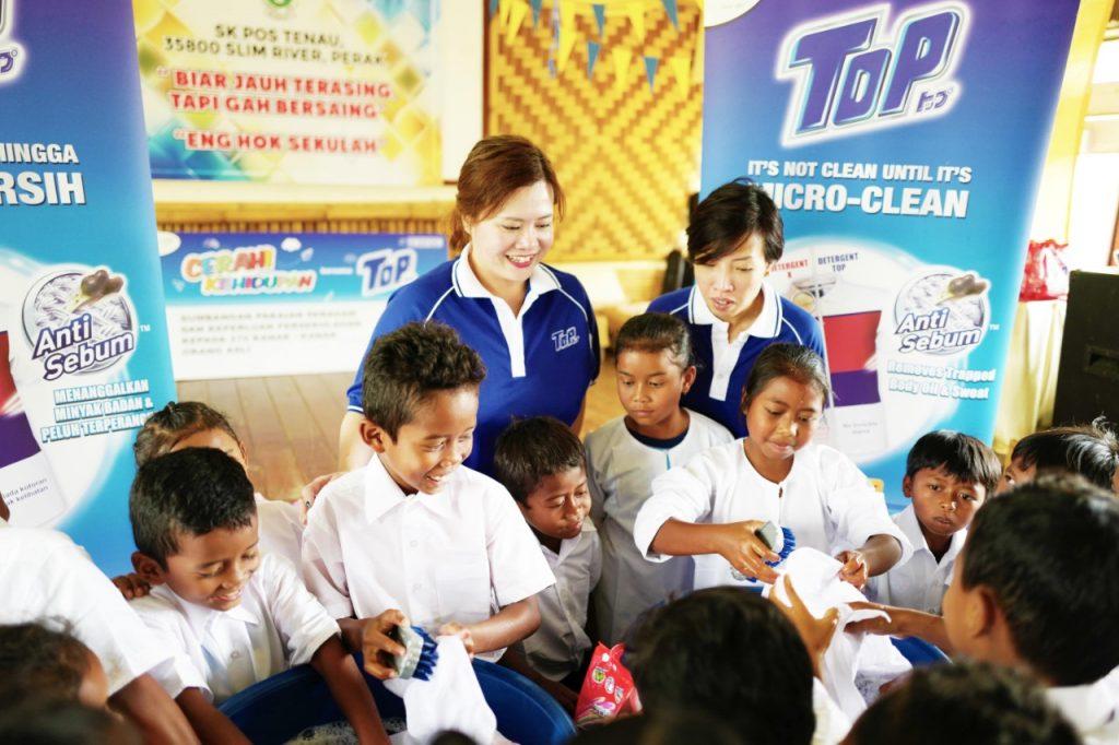 Pelajar Orang Asli di SK Pos Tenau gembira menyertai bengkel mencuci pakaian yang dikendalikan oleh Pengurus Pemasaran (Divisyen Penjagaan Fabrik) Southern Lion Sdn Bhd, Ling Ai Li.